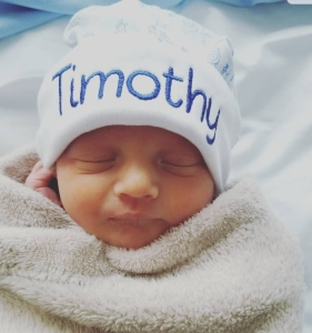"Sleeping newborn baby wrapped in a blanket wearing a blue and white hat that says ""Timothy""."