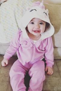18 month old girl with curly hair wearing a purple unicorn sweatsuit