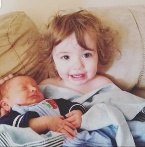 16 Month old curly hair girl holding her newborn brother