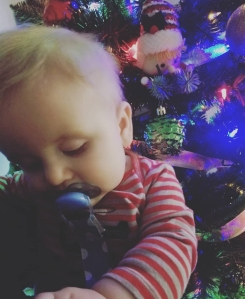 8 month old with a soother in her mouth in front of the Christmas tree