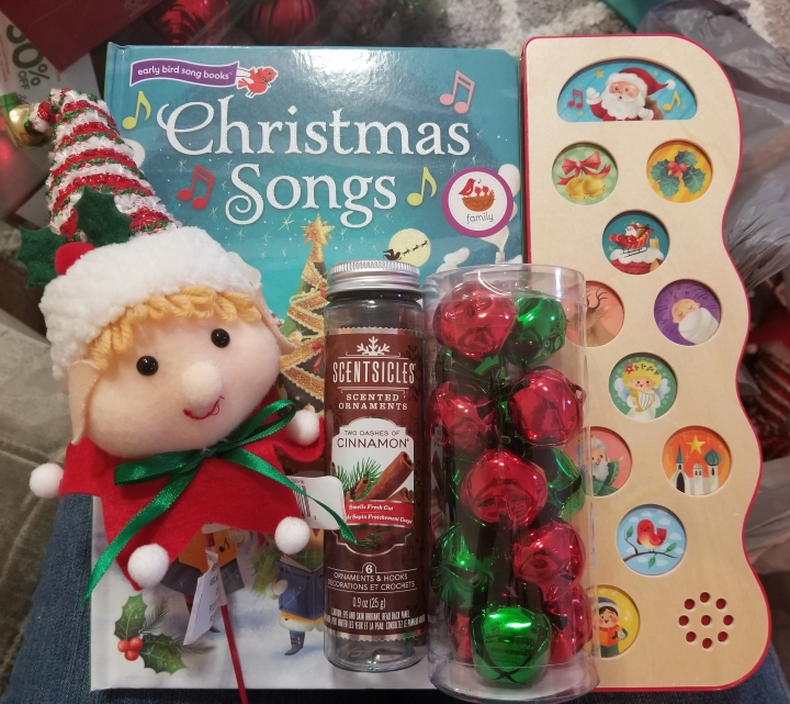 Christmas song book. Elf ornament with a red, green, and white hat with a bell on it,. Green and red Christmas bells. Scented cinnamon sticks for the tree.