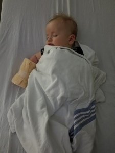 Timothy at 4 months old laying wrapped in a hospital blanket sleeping with an IV in.