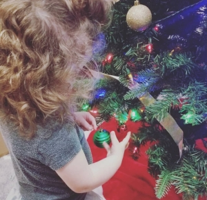 Curly brown haired two year old girl placing a green Christmas ornament on the Christmas tree.