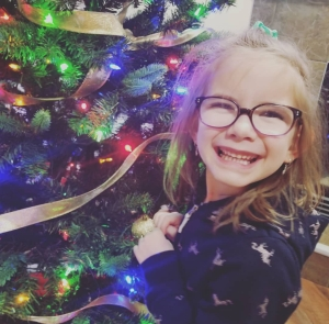 Brown haired 6 year old girl in a pony tail and glasses smiling in front of the Christmas tree.