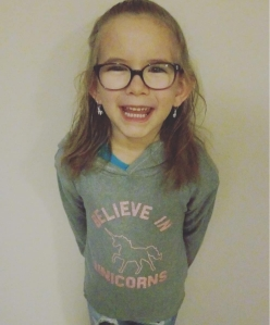 6 year old Hailey with her brown hair in a pony tail, wearing glasses, and smiling.