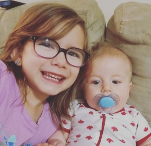 Hailey with her brown hair down, wearing glasses and a purple shirt. She is smiling beside her brother Timothy. He has blonde hair and is wearing a Canada Day onesie.