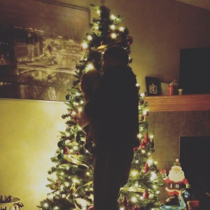 Lit up Christmas tree with a silhouette of a dad holding his infant baby boy in front.