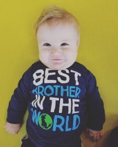 Timothy a blonde haired blue eyed 8 month old. He is smiling. His blue shirt says best brother in the world.