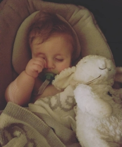 Timothy laying in his bassinet with a blanket and sheep stuffy. Timothy is rubbing his right eye.