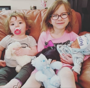 Hailey, Charlotte, and Timothy. Hailey is holding brand new Timothy. Charlotte is sitting beside them.
