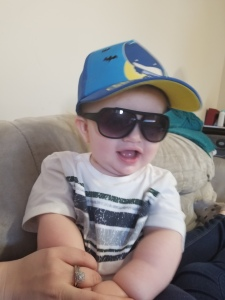 Timothy is sitting on the couch. He is wearing a t shirt, a blue batman baseball cap, and black sunglasses. He is smiling.