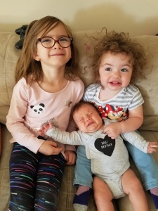 Hailey, Charlotte, and Timothy at 6 weeks. Hailey and Charlotte are smiling. Timothy is crying.