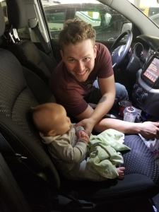 James sitting in the car with Timothy at 6 months sitting in the passenger seat. We are parked.