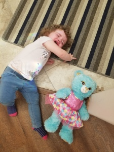 Charlotte laying on the ground throwing a tantrum beside a teddy bear.