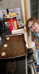 Photo of Hailey placing Easter cookies onto a baking sheet with a plate full of baked cookies beside her.