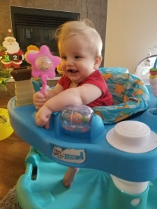 Timothy at 8 months old smiling and playing in his exersaucer.