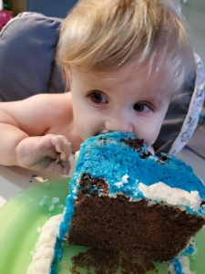 Timothy on his first birthday leaning mouth first into a corner of his blue birthday cake.