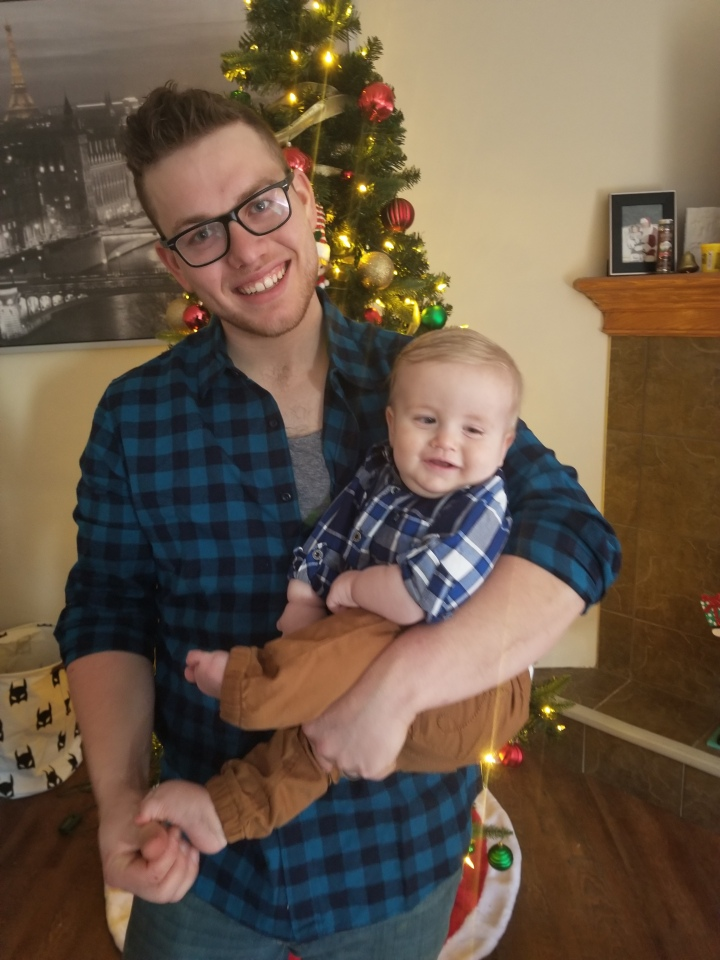 A photo of James and Timothy in front of the Christmas tree wearing blue plaid shirts.