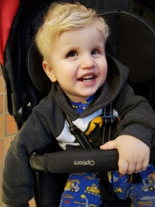 Photo of Timothy sitting in his stroller with a big smile on his face.