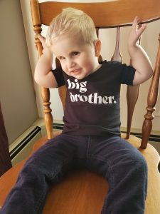"""Photo of Timothy sitting on a chair smiling wearing a black t shirt that says """"big brother""""."""