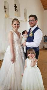 Photo at our wedding of James holding Charlotte standing beside me while Hailey stands in front of us.