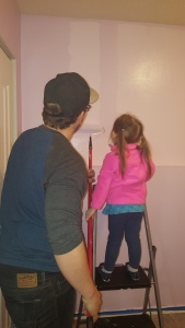 Photo from behind of James helping Hailey paint her wall purple in our first place together.