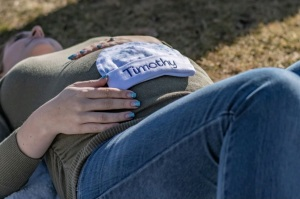 """Photo from my maternity pictures laying on my back with a baby hat that says """"Timothy"""" laying on my pregnant belly."""